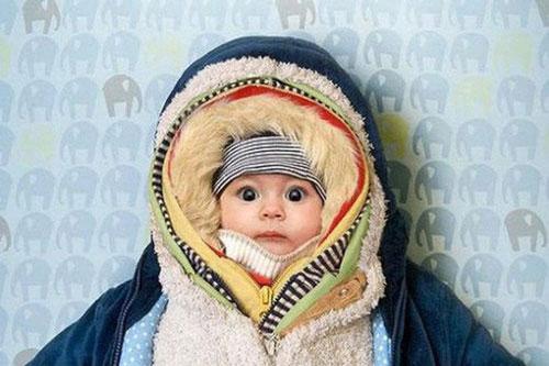 Ủ quá nhiều lớp quần áo để giữ ấm cho trẻ không phải cách tốt.