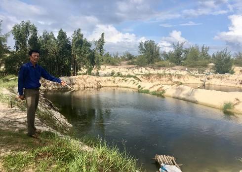 Ông Võ Văn Khiêm bên hồ nuôi cá lóc trên cát của gia đình.