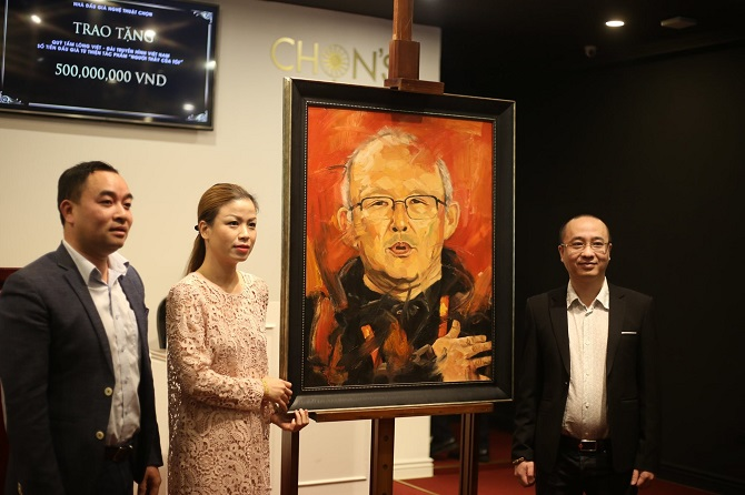 Ông Nguyễn Phan Huy Khôi, đại diện Tập đoàn Bảo Ninh (bên phải) đã đấu giá thành công bức tranh Người thầy của tôi với giá 12.000 USD và ủng hộ thêm hơn 221 triệu đồng cho Quỹ Tấm lòng Việt.