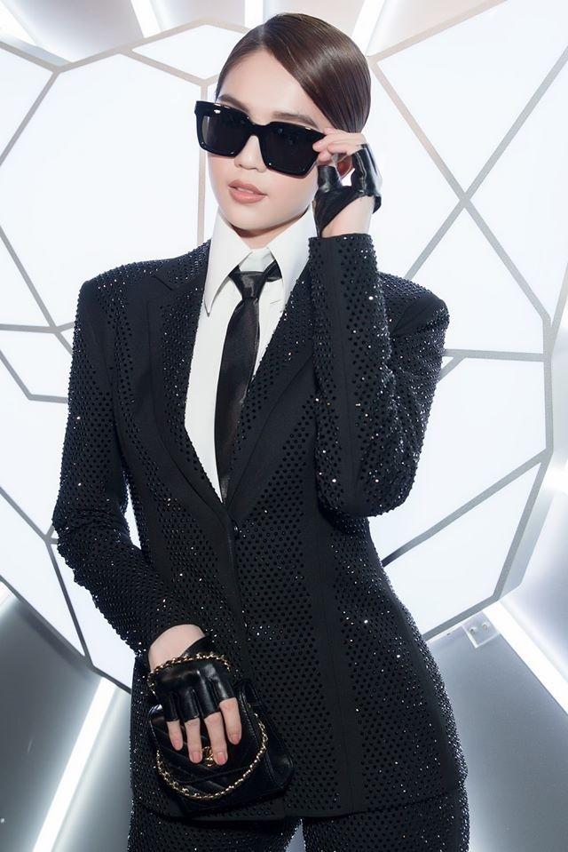 Không cần váy áo lộng lẫy, Ngọc Trinh vẫn xuất hiện cực chất trong bộ suit đen đính đá lấp lánh. Việc kết hợp phụ kiện gồm kính mắt đen, túi xách, cà vạt và bao tay da khiến tổng thể trở nên ấn tượng hơn.