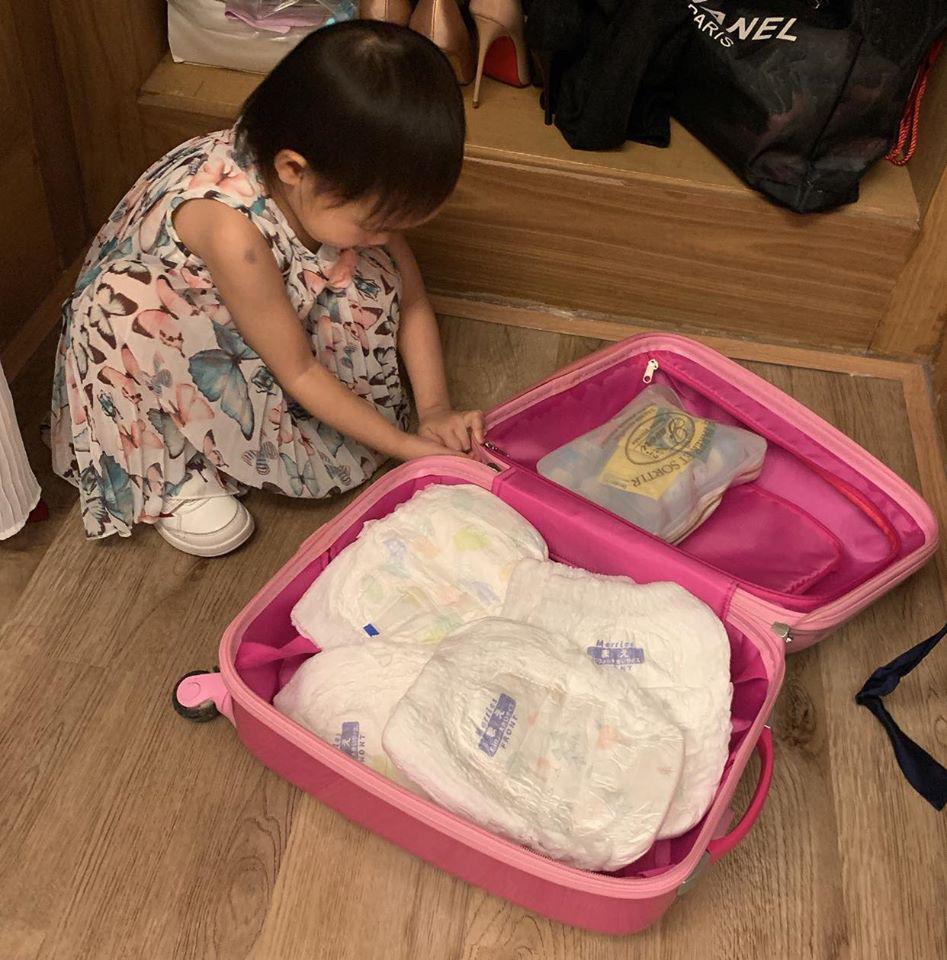 Cô bé tự sắp xếp hành lý, gấp quần áo của mình.
