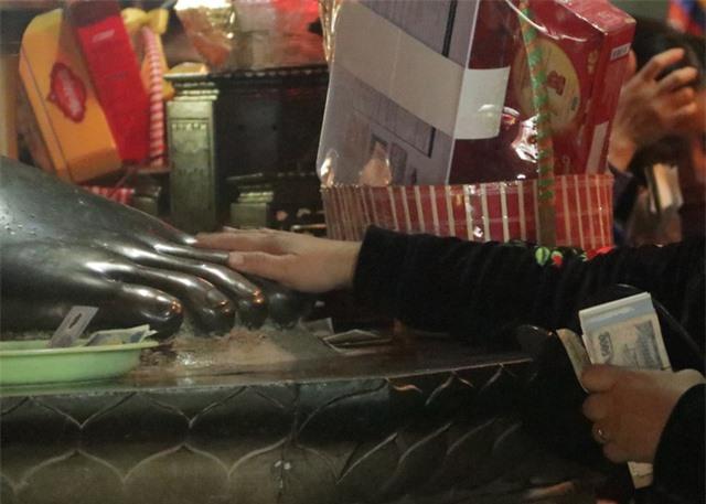Chen chúc xếp hàng xoa tiền lên chân tượng Phật cầu may ở Hà Nội - 7