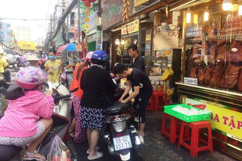 Người dân TPHCM mua nhiều heo quay, vịt quay trong ngày vía Thần tài. Ảnh: Đại Việt.