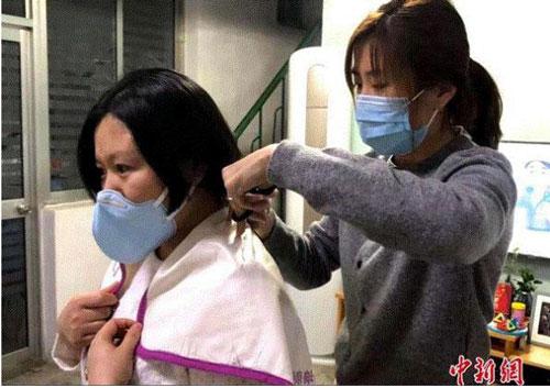 Trước khi lên đường chiến đấu với bệnh dịch, một y tá bệnh viện thuộc Đại học Sơn Đông (Tế Nam, Trung Quốc) cắt đi mái tóc dài của mình để thuận tiện làm việc. (Ảnh: Chinanews)
