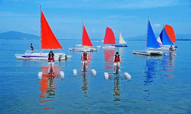 Du khách thỏa sức trải nghiệm với việc điều khiển thuyền buồm catamaran hay đạp xe đạp nước.