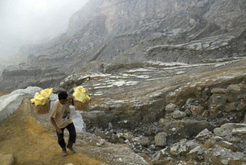 Một người thợ mỏ đang gánh những tảng lưu huỳnh nặng khoảng 70kg.