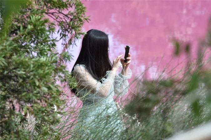 Một phụ nữ trẻ đang chụp ảnh bên hồ nước màu hồng trong công viên Westgate. Du khách thường xuyên tới đây để chụp ảnh hiện tượng hồ nước đổi màu kỳ thú này.