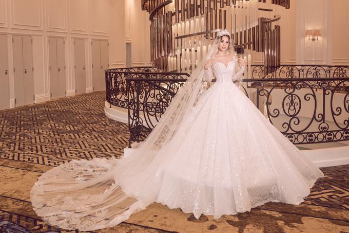 Hoa hậu Tiểu Vy có dịp hóa thân thành cô dâu khi diện các váy cưới trong bộ sưu tập xuân hè sắp ra mắt của NTK Phạm Đăng Anh Thư. Bộ đầm đầu tiên mang phom dáng xòe phồng, được dựng gọng corset 12 mảnh giúp người đẹp khoe vóc dáng đồng hồ cát.