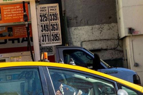 Một tài xế taxi đeo găng tay cao su vào đổ xăng trong khi giá xăng đã giảm do Covid-19 tại New York, Mỹ, ngày 14/3. Ảnh: Getty.