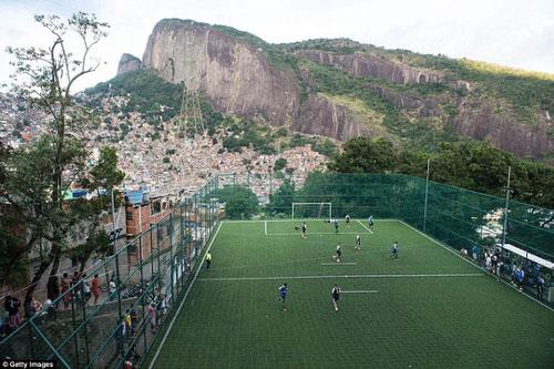 """Là đất nước được mệnh danh """"cái nôi của làng túc cầu"""", Brazil sở hữu những sân vận động đẳng cấp diễn ra World Cup 2014. Ngoài ra, người dân ở đất nước này còn có một tình yêu mãnh liệt với bóng đá. Tại Rocinha - khu ổ chuột lớn nhất và đông dân nhất Brazil, có một sân bóng đẹp được bao quanh bởi núi đá, phục vụ niềm đam mê với môn thể """"vua"""" của người dân địa phương."""
