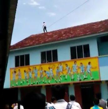Hình ảnh nam sinh trèo lên nóc nhà đòi tự tử.