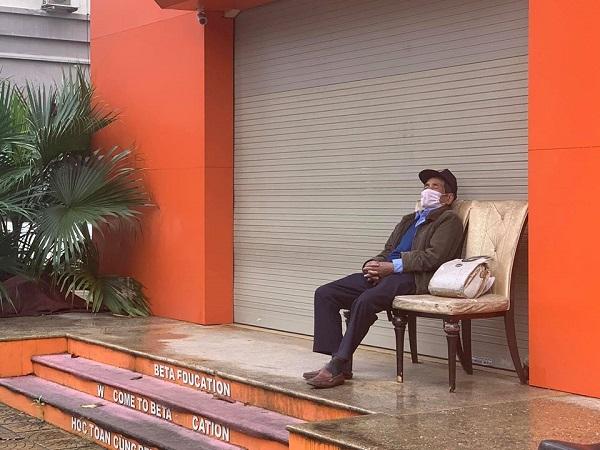 Một cửa hàng trên phố đóng cửa do dịch bệnh, chỉ có bác bảo vệ ngồi ngủ gật.