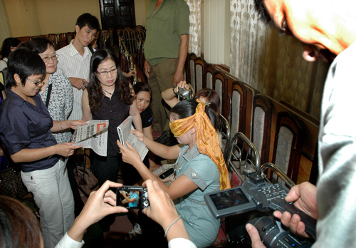 Chị Hoàng Thị Thiêm bịt mắt đọc báo trước ống kính phóng viên và ghi nhận của các nhà khoa học.