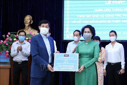 Tiếp nhận tượng trưng số tiền ủng hộ công tác phòng chống dịch COVID-19 của ông Jonathan Hạnh Nguyễn, Chủ tịch Tập đoàn Liên Thái Bình Dương. (Ảnh: TTXVN)