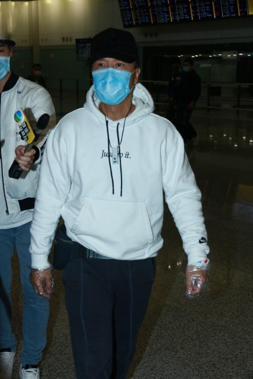 Vợ chồng Chân Tử Đan và hai con từ Mỹ về Hong Kong sáng 20/3. Bốn người đeo khẩu trang, đeo kính và che chắn kín mít, máy lọc không khí mini đeo trên cổ.