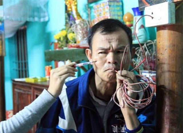 Ông Dương Đình Thắng ngậm dây diện rồi dùng bút thử điện gí vào người. Kết quả: Bút thử điện sáng đèn.