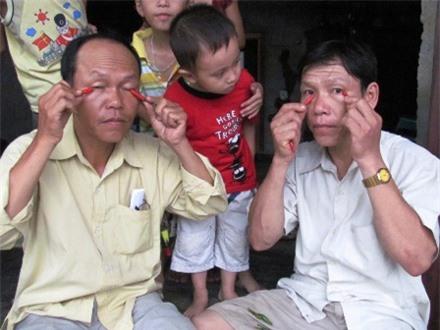 Anh Vinh (trái) và anh Khánh bắt đầu màn ăn ớt thay cơm và chà ớt lên mắt