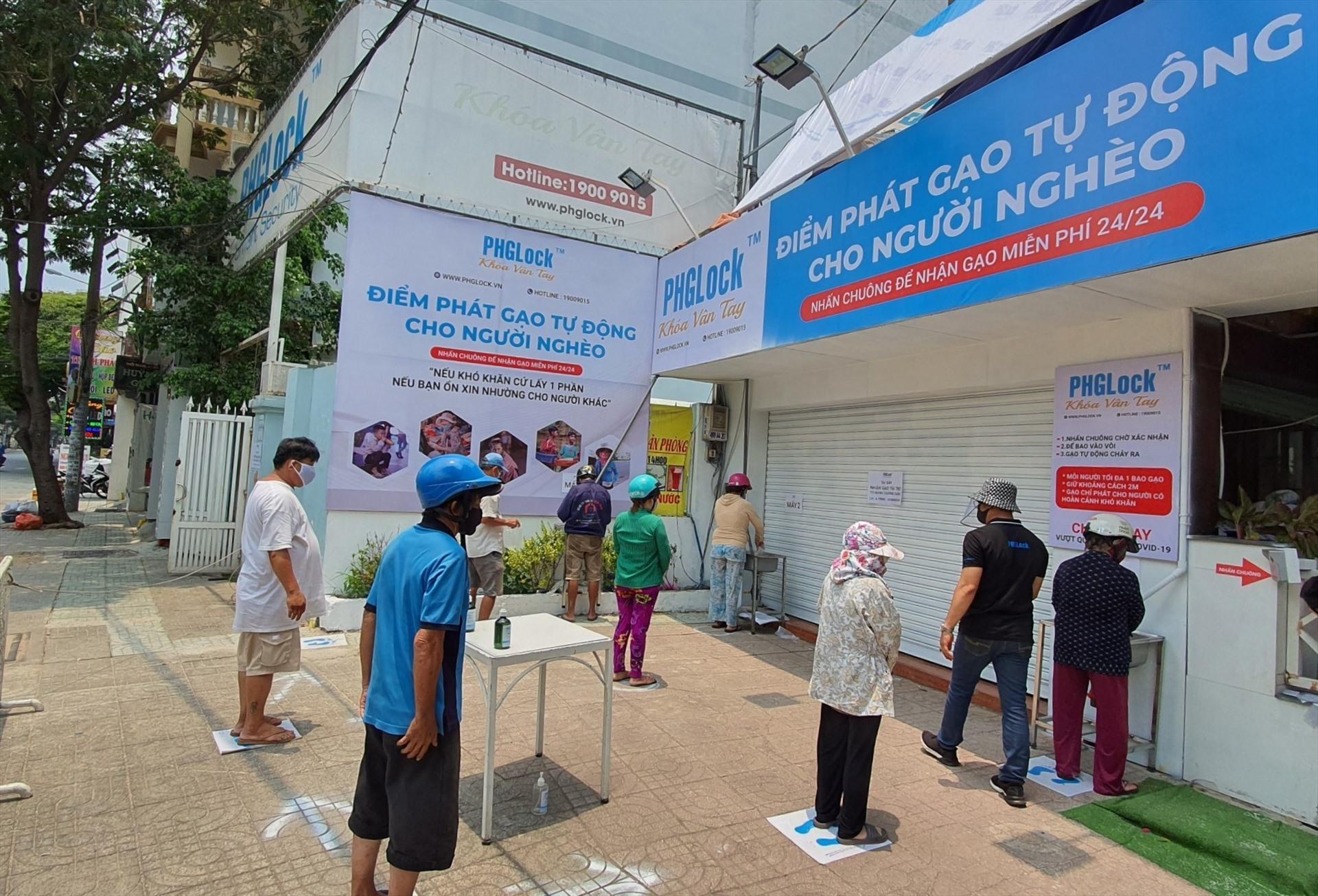 """Người dân xếp hàng chờ lấy gạo miễn phí tại """"ATM gạo"""" Tân Phú."""