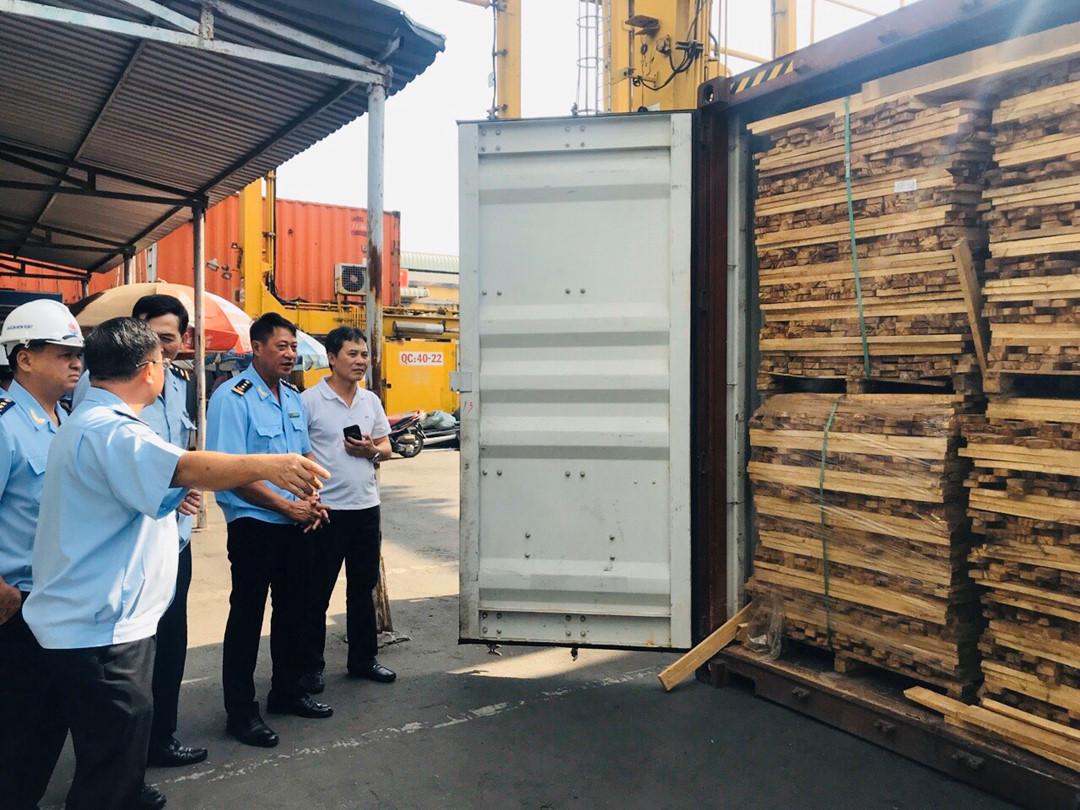 Ông Trần Việt Thắng (thứ 2 từ phải sang) đang chỉ đạo khui lô hàng gỗ xẻ trốn thuế tại cảng Cát Lái. (Ảnh: T.H)
