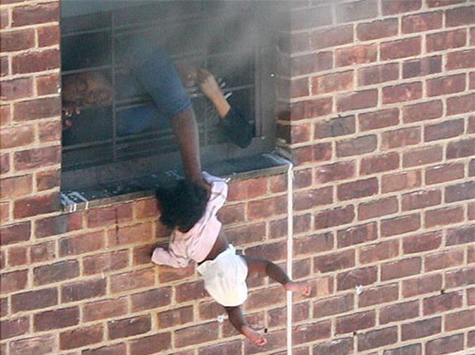 Bức ảnh đứa trẻ 7 tháng tuổi bị thả lủng lẳng bên ngoài cửa sổ khiến nhiều người xót xa nhưng nhìn kỹ hơn mới nhận ra sự thật không như tưởng tượng - Ảnh 1.