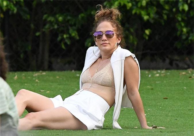 J.Lo tranh thủ lúc khách chưa đến, cởi áo nằm tắm nắng trên bãi cỏ.