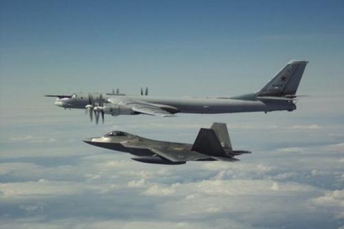 Tiêm kích tàng hình F-22A Raptor của Mỹ bay kèm máy bay ném bom chiến lược Tu-95MS của Nga. Ảnh: Avia-pro.
