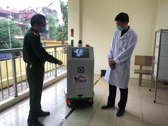 PGS.TS Đại tá Tăng Quốc Nam - Chủ nhiệm đề tài (bên trái) giới thiệu rô-bốt tới các bác sĩ bệnh viện Bắc Thăng Long.