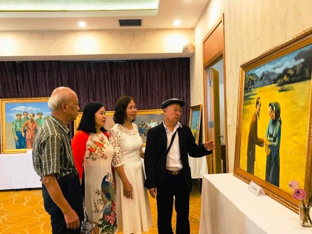 Họa sĩ Thái Hòa (ngoài cùng bên phải) giới thiệu về các tác phẩm của ông.