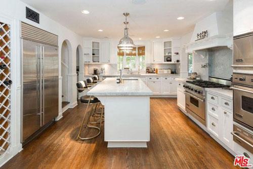 Nhà bếp rộng lớn, thoáng đãng, được trang bị nhiều công cụ nấu nướng hiện đại tích hợp trong những chiếc tủ âm tường khổng lồ.