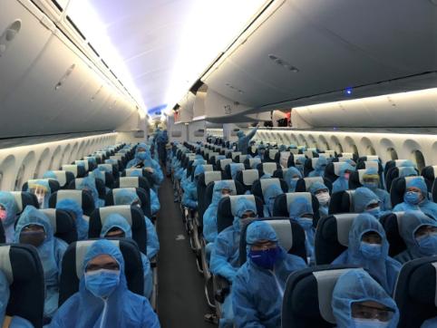 Tất cả hành khách, phi hành đoàn sử dụng đồ bảo hộ toàn thân và hạn chế giao tiếp, đi lại trong suốt chuyến bay. Ảnh: VNA.