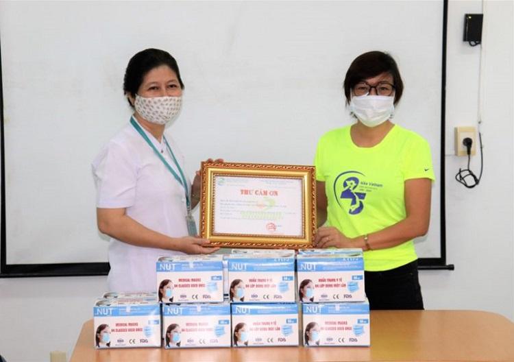 Bà Vũ Thủy, Giám đốc đối ngoại Nike Việt Nam (bên phải) trao tặng khẩu trang y tế cho đội ngũ y bác sĩ tại Bệnh viện Nhiệt đới TP. Hồ Chí Minh.