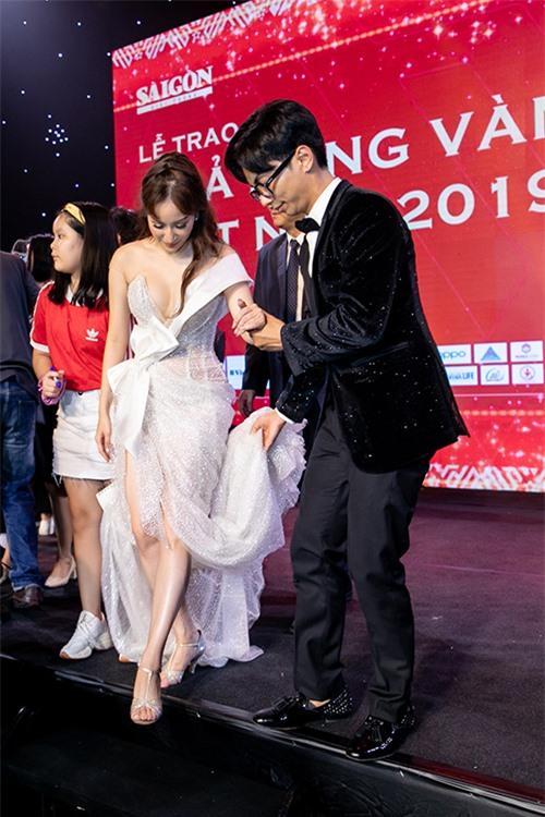 Phan Hiển đỡ váy, dắt tay vợ bước xuống cầu thang khi kết thúc phần trao giải.
