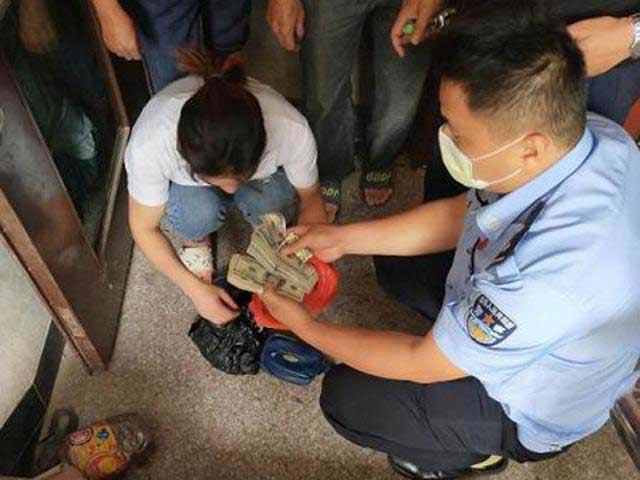 Cảnh sát trả lại cho ông Chen số tiền đã giấu trên trần nhà tắm.