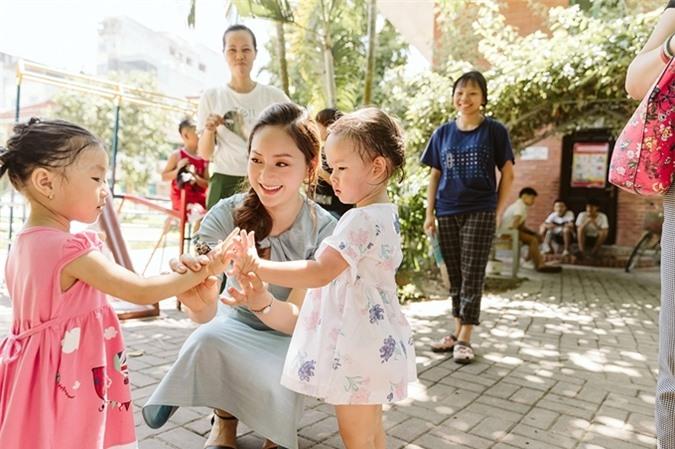 Nữ diễn viên hướng dẫn con nói từ bạn và dạy con giao lưu với các em nhỏ tại làng trẻ cũng như các em nhỏ theo bố mẹ tới dự hoạt động.