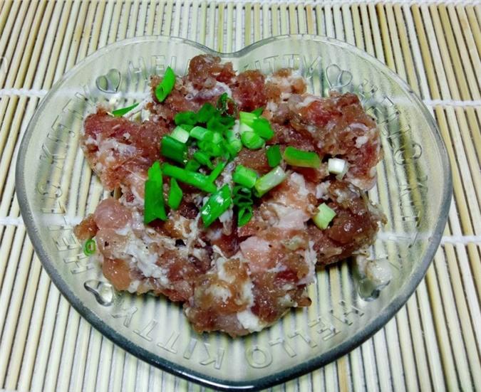 Thịt heo xay ướp với muối, bột nêm, tiêu, hành tím băm nhuyễn và chút hành lá để trong 20 phút cho thịt heo ngấm gia vị. Sau đó, bạn viên thịt thành những hình tròn to hơn ngón tay cái một chút, để riêng ra một đĩa.
