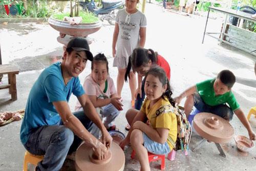 Anh Tuấn cùng các em nhỏ tập làm gốm sứ.