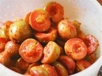 Cho thêm bột ớt vào mận đã ngấm gia vị rồi lắc đều là hoàn tất món ăn