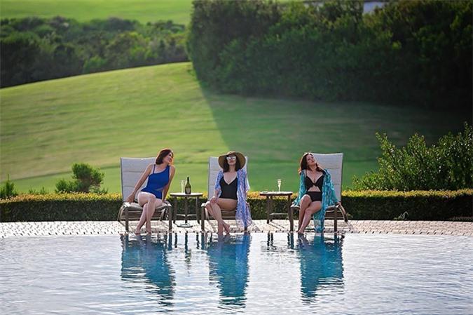 Resort họ ở phong cảnh tuyệt đẹp. Bộ ba mặc áo tắm ngồi uống rượu, tám chuyện bên hồ bơi.