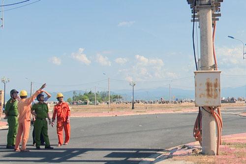 Lực lượng chức năng kiểm tra, khám nghiệm hiện trường các vị trí TBA bị cắt trộm cáp điện. Ảnh: TTXVN.