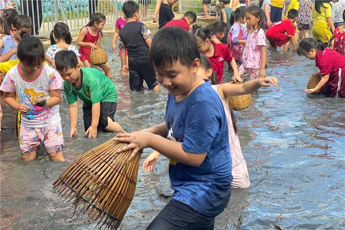 Cà Pháo không ngại lội xuống sình, dùng nơm bắt cá. Đìa cá này do nhà trường dựng lên, có giáo viên và phụ huynh giám sát nên đảm bảo an toàn cho các em học sinh.
