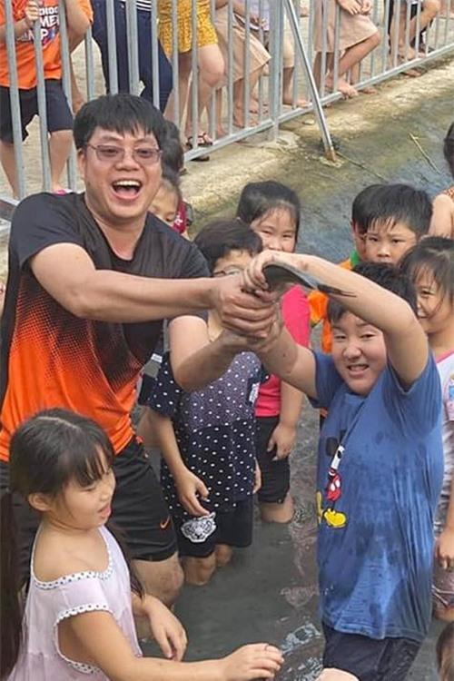 Cà Pháo tay không bắt và cầm con cá với vẻ mặt đầy phấn khích. Nhiều bạn bè tỏ ra ngưỡng mộ cậu bé trước thành tích bắt cá.