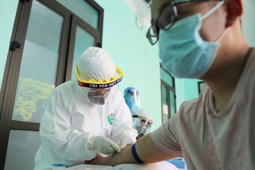Nhân viên y tế lấy mẫu máu để xét nghiệm cho người dân. (Ảnh: TTXVN)