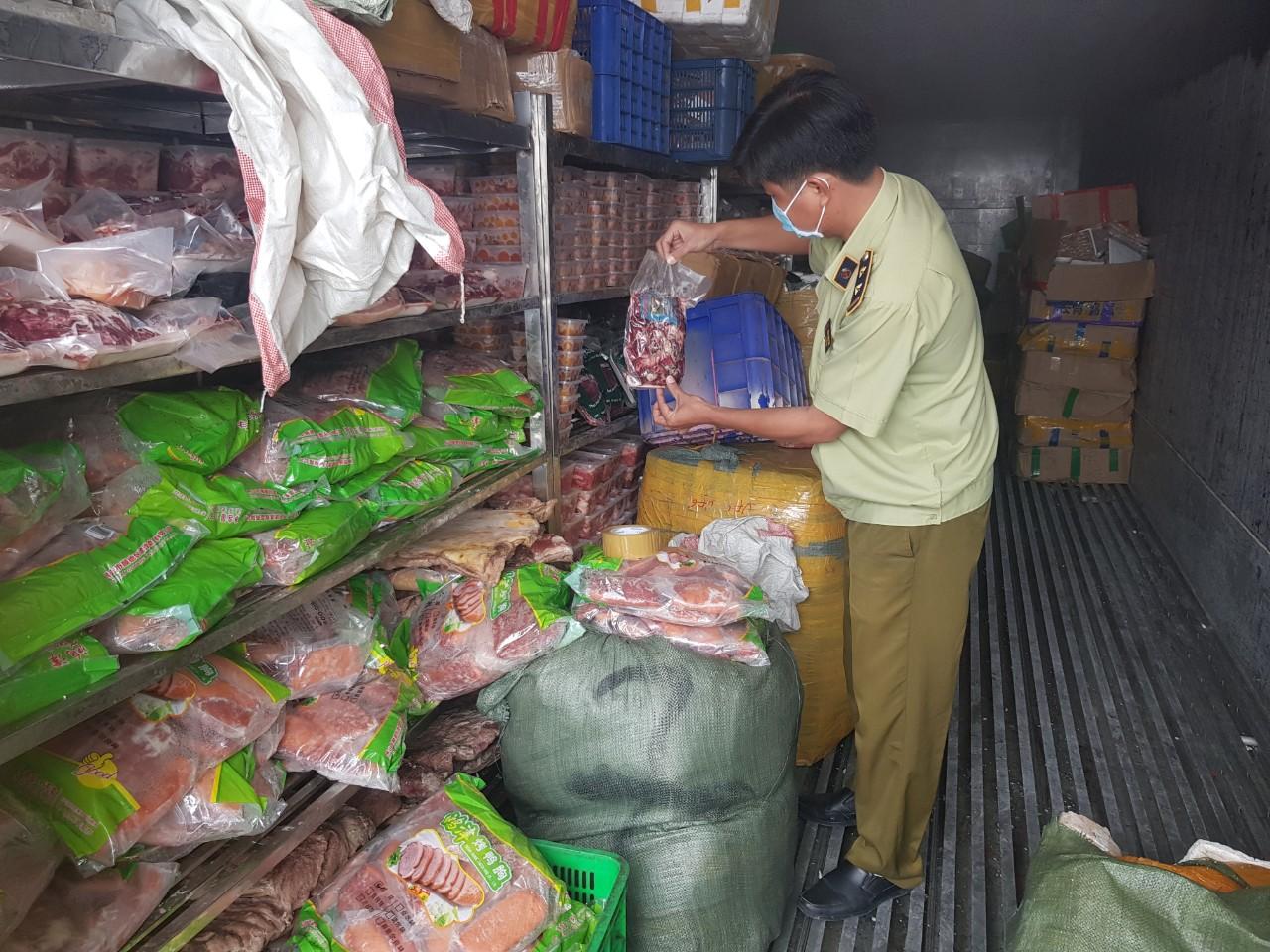 Lực lượng chức năng kiểm tra và thu giữ các mặt hàng thực phẩm đông lạnh vi phạm.