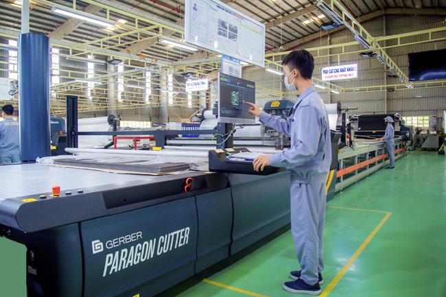 Công nhân điều khiển máy cắt vải CNC tại nhà máy ghế ô tô