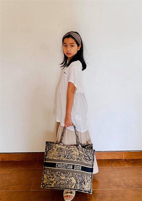 Lưu Hương Giang cho biết, Mina lôi hết tủ quần áo của mẹ ra để thử tài mix & match. Cô bé thử nghiệm phong cách bà thím khi kết hợp Christian Dior Tote Bag với băng đô màu đồng điệu, dép lê đính cùng áo phông oversized và chân váy.