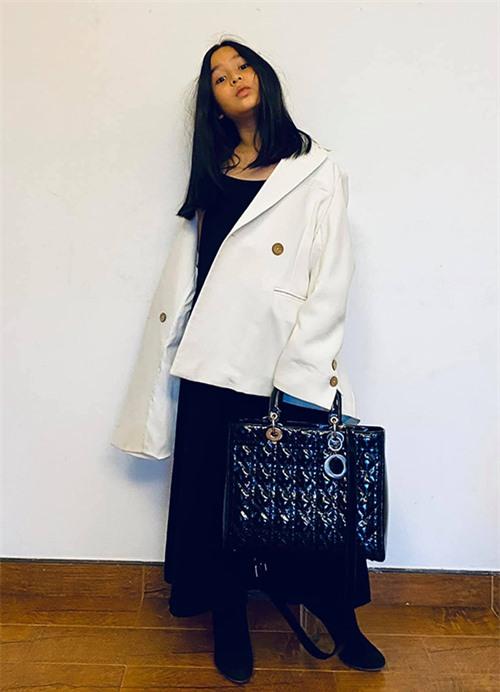 Mina trông như một fashionista cá tính khi diện blazer trắng với váy hai dây đen trùm boot thấp cổ và túi hàng hiệu cùng màu. Các item cùng màu nhưng khác chất liệu tạo nên sự đồng điệu nhưng không nhàm chán trên một set đồ.