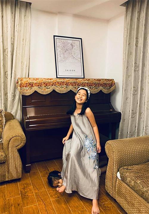 Lúc khác, Mina lại biến thành cô gái thùy mị nữ tính với váy lụa thêu hoa kết hợp băng đô cùng màu. Bé Misu, em gái của Mina, nghịch ngợm lăn lê dưới sàn nhà trong khi chị tạo dáng.