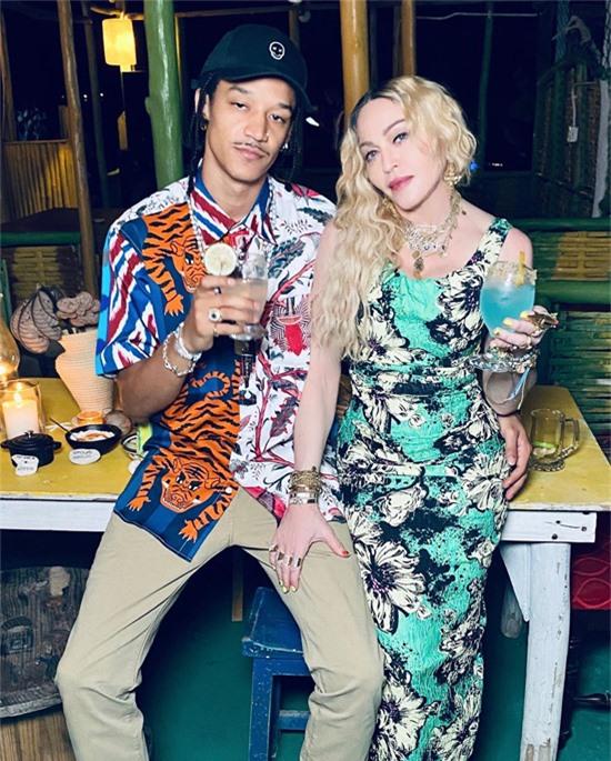 Madonna mặc bộ đầm hoa lộng lẫy, ngồi trong vòng tay của chàng vũ công Ahlamalik Williams trong bữa tiệc sinh nhật 62 tuổi của cô ở Jamaica hôm 16/8.