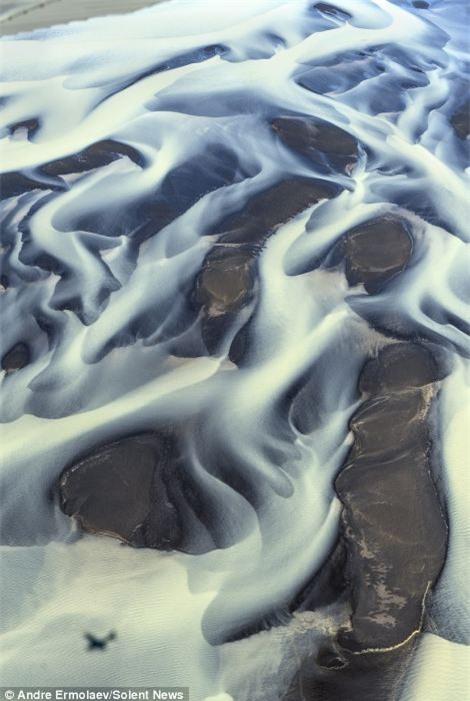 Nước sông tràn lên trên bề mặt cát bằng phẳng trông tựa như những đám mây