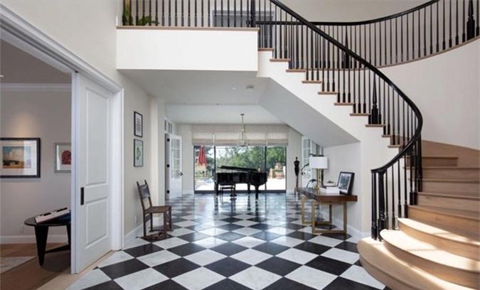 Tiền sảnh lớn nổi bật với đá caro đen trắng, cầu thang uốn cong thanh lịch.